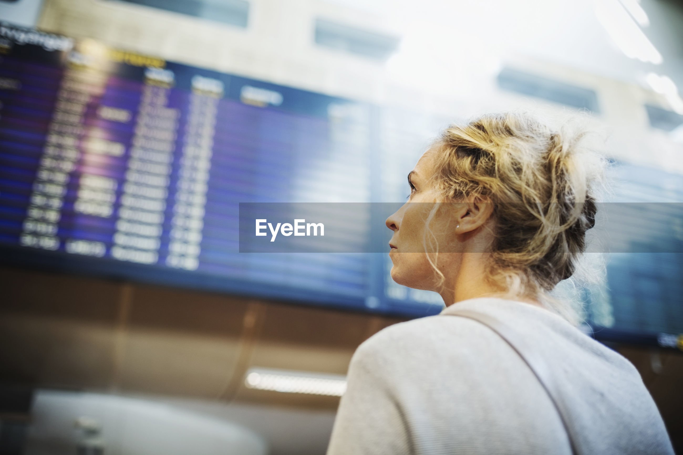 Rear view of businesswoman looking at arrival departure board in airport