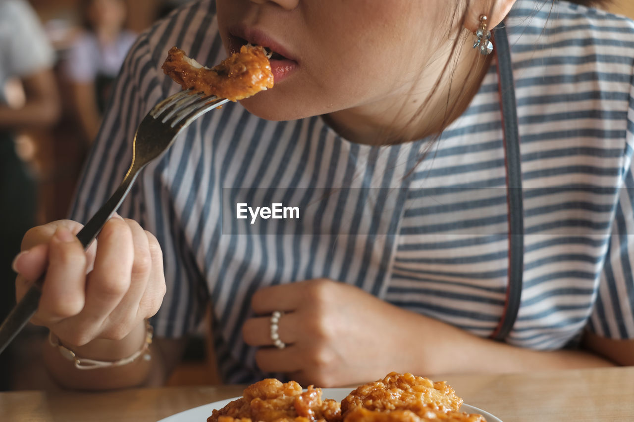 Midsection of young woman eating food in restaurant