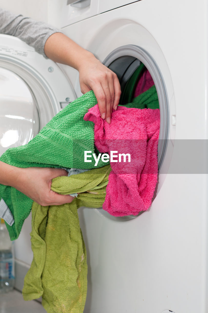 Cropped hand putting clothes in washing machine