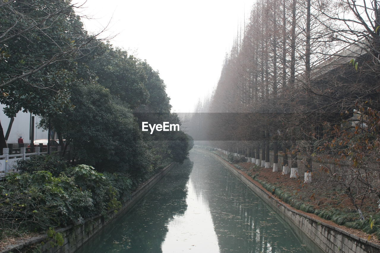 Calm Canal Amidst Trees Against Sky During Foggy Weather