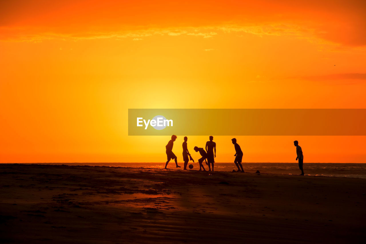 Silhouette Of People On Beach At Sunset