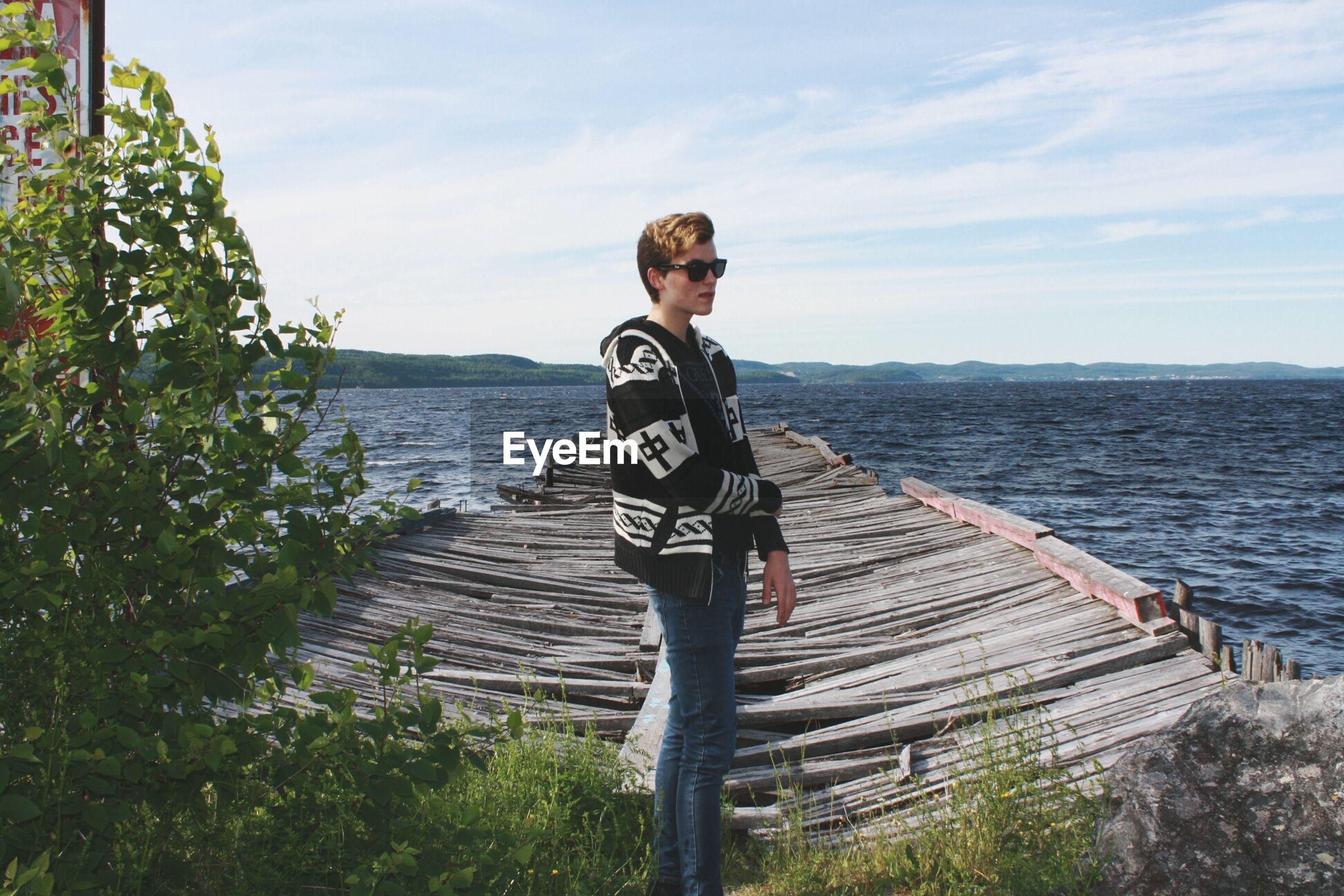 Young man standing broken pier on sea against sky