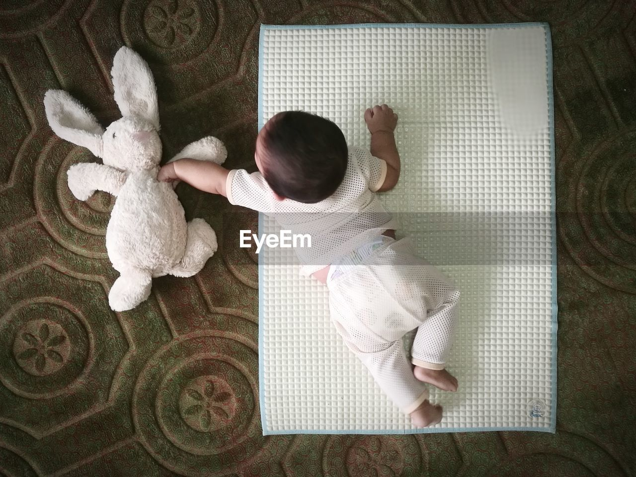 Directly Above Shot Of Baby Boy Playing With Stuffed Toy While Lying On Mat