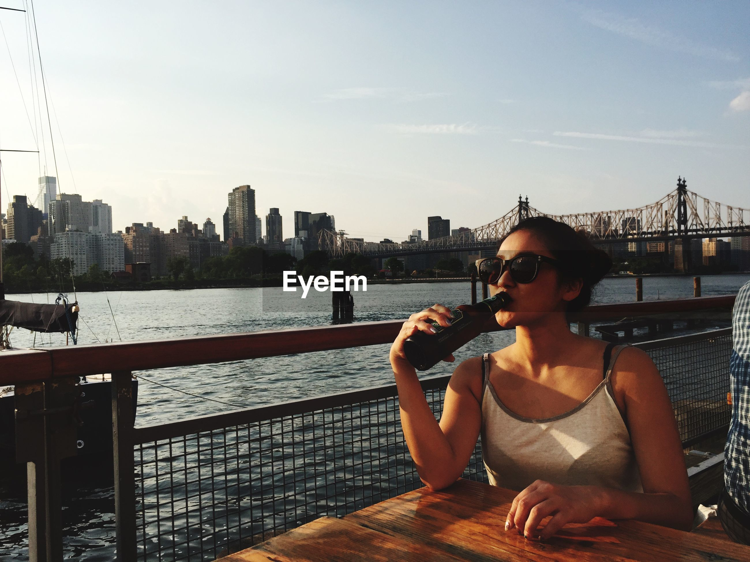 water, lifestyles, architecture, built structure, building exterior, young adult, city, leisure activity, railing, river, person, sky, young women, sitting, casual clothing, cityscape, connection, standing