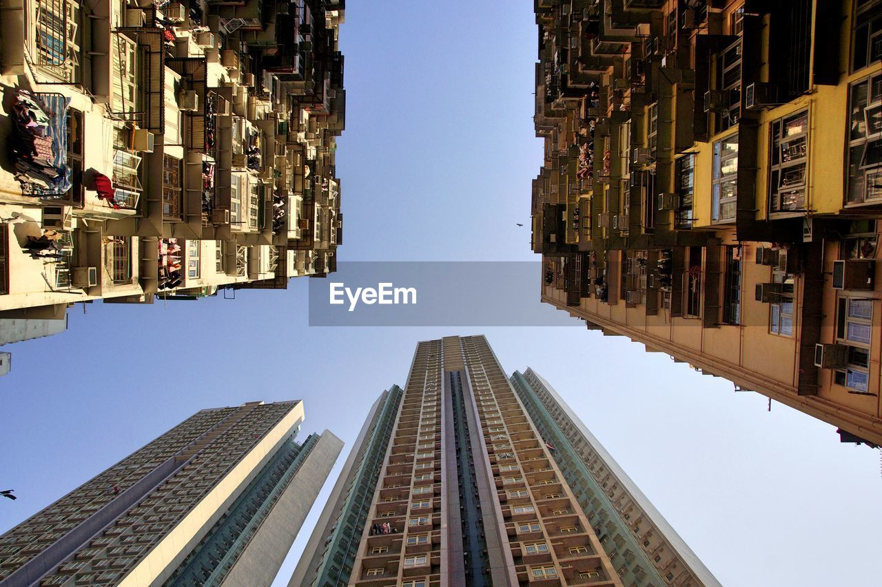 Directly Below Shot Of Buildings Against Clear Sky