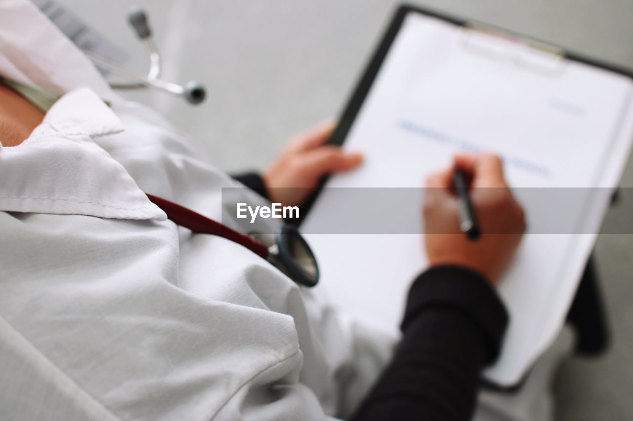 High angle view of doctor writing on report over clipboard