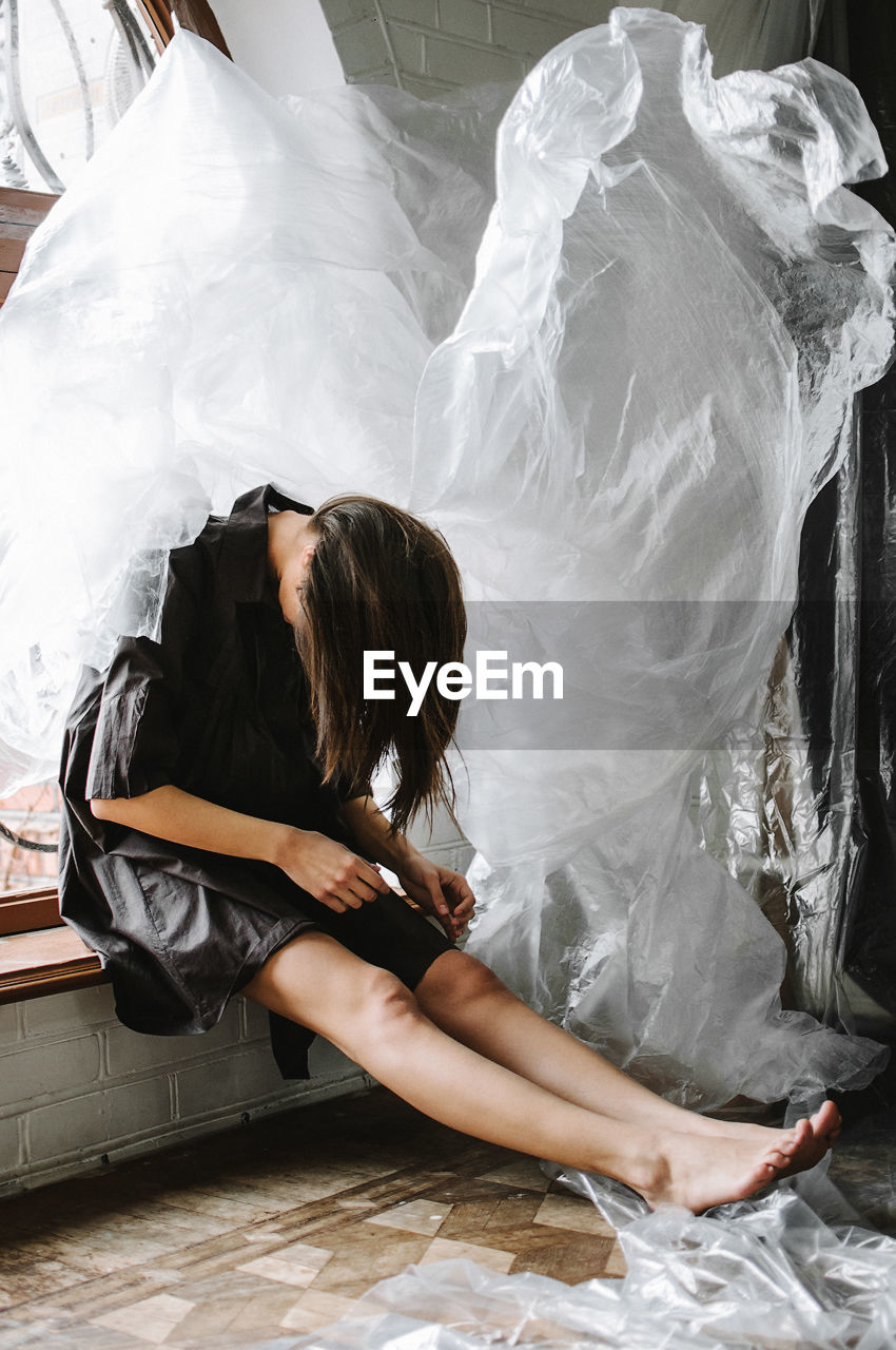 Woman sitting with face down by plastic