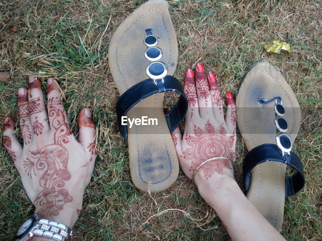 human leg, human body part, human foot, real people, low section, day, high angle view, outdoors, grass, personal perspective, women, field, one person, men, lifestyles, shoe, human hand, close-up, adult, people
