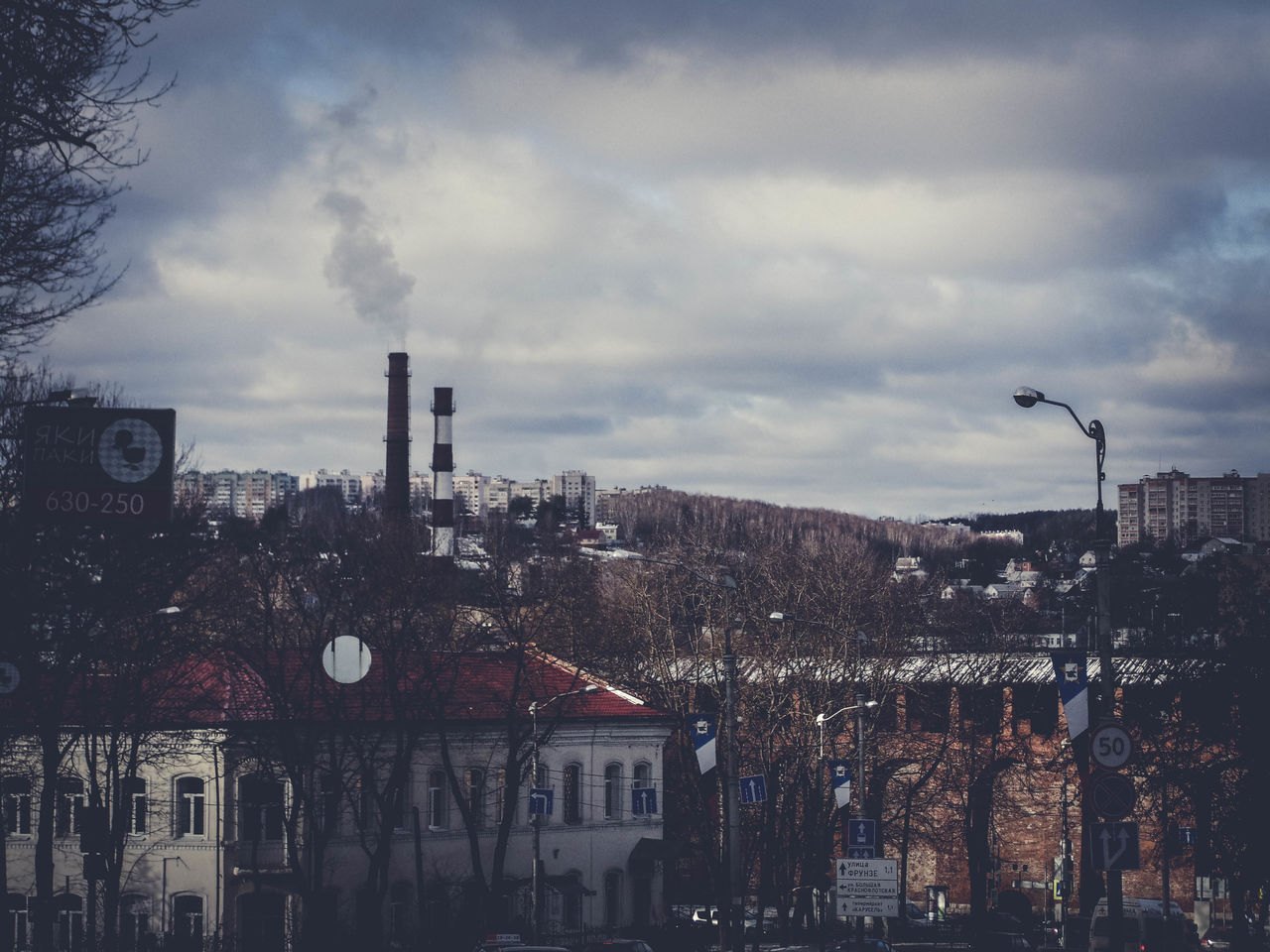 architecture, building exterior, sky, cloud - sky, built structure, city, building, nature, no people, street, outdoors, industry, street light, day, residential district, cityscape, smoke stack, factory, tall - high, pollution