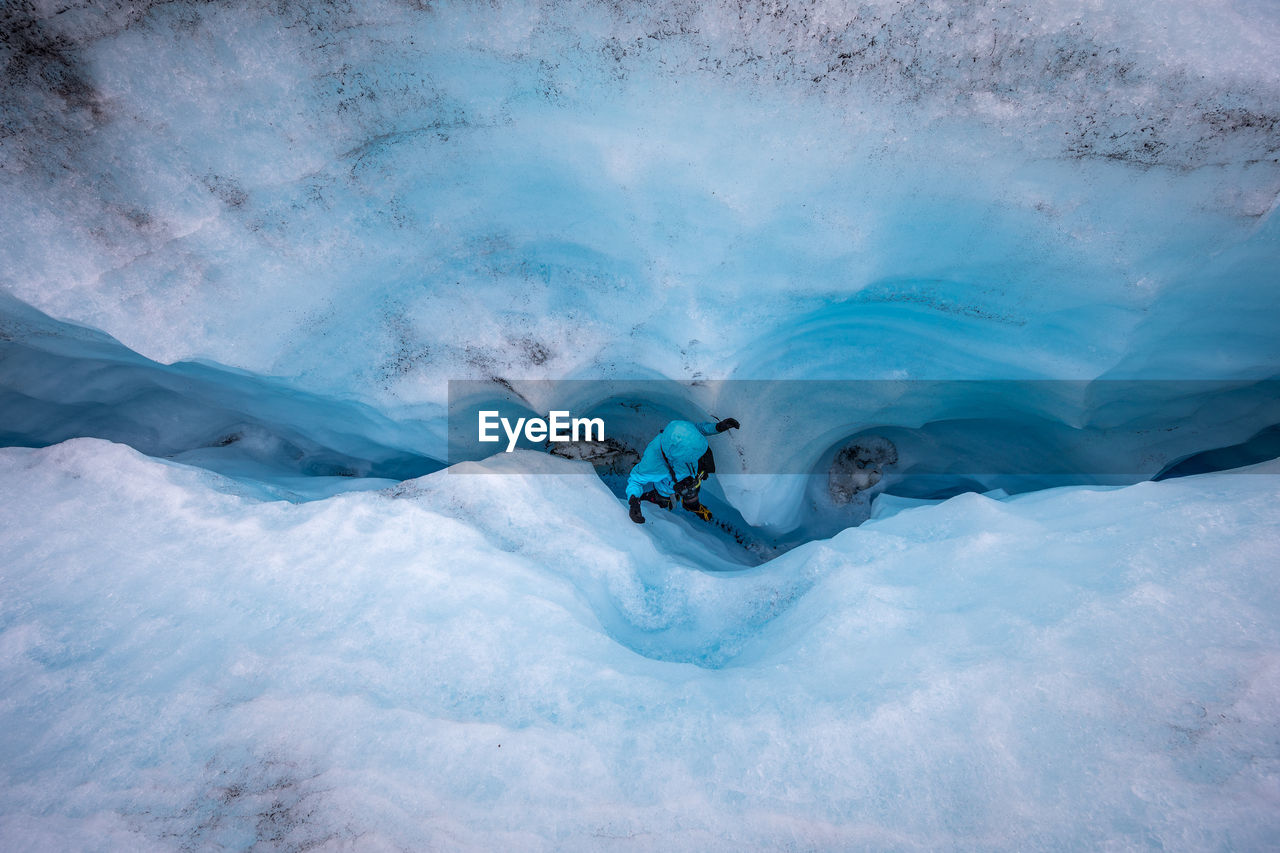 High Angle View Of Person Walking Amidst Glacier