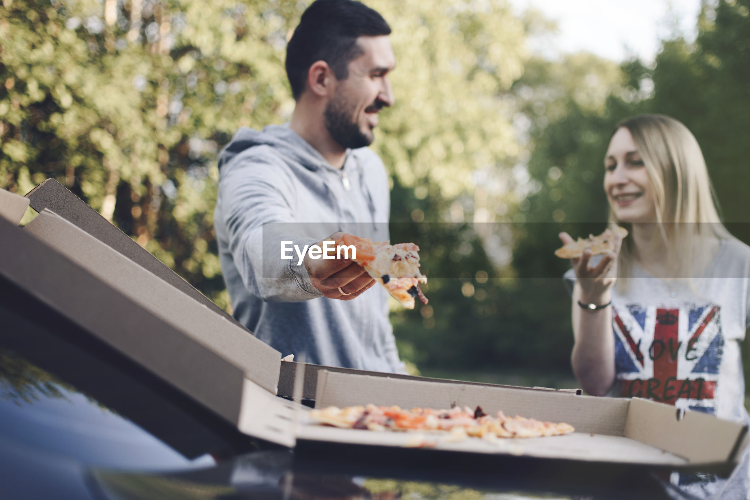 Couple eating pizza while standing against trees at park