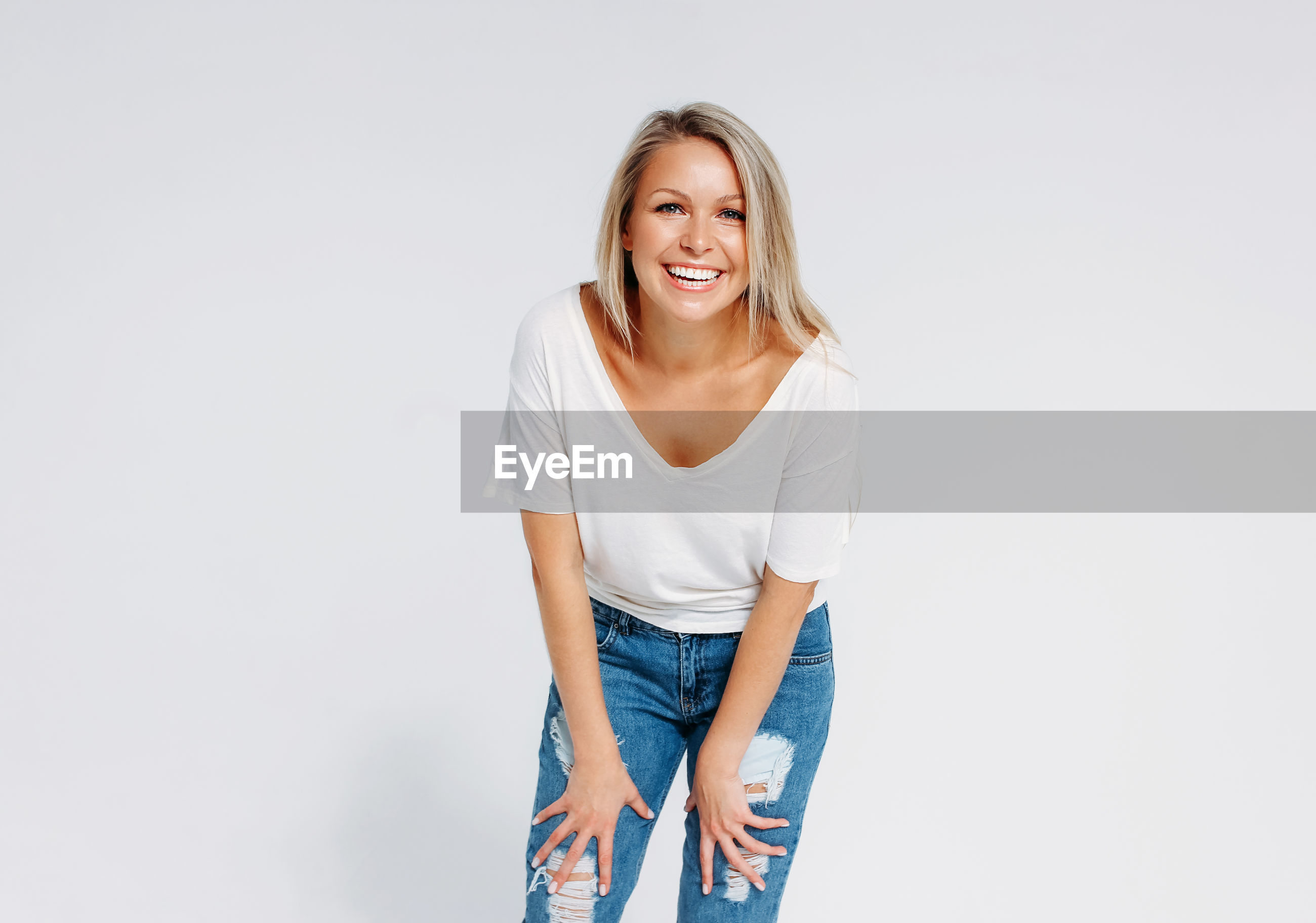 PORTRAIT OF HAPPY YOUNG WOMAN AGAINST WHITE BACKGROUND
