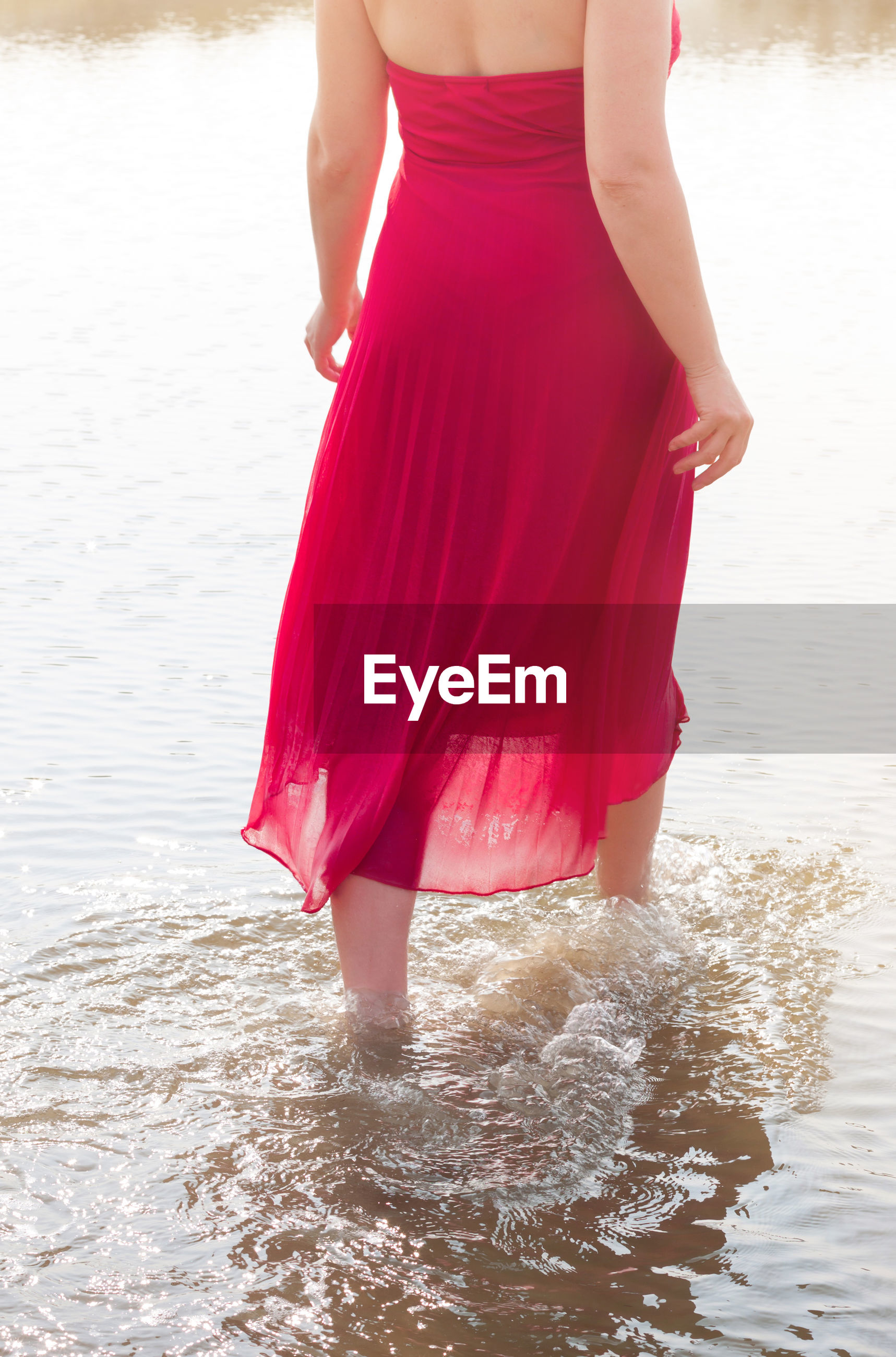 Midsection of woman in red dress wading in sea