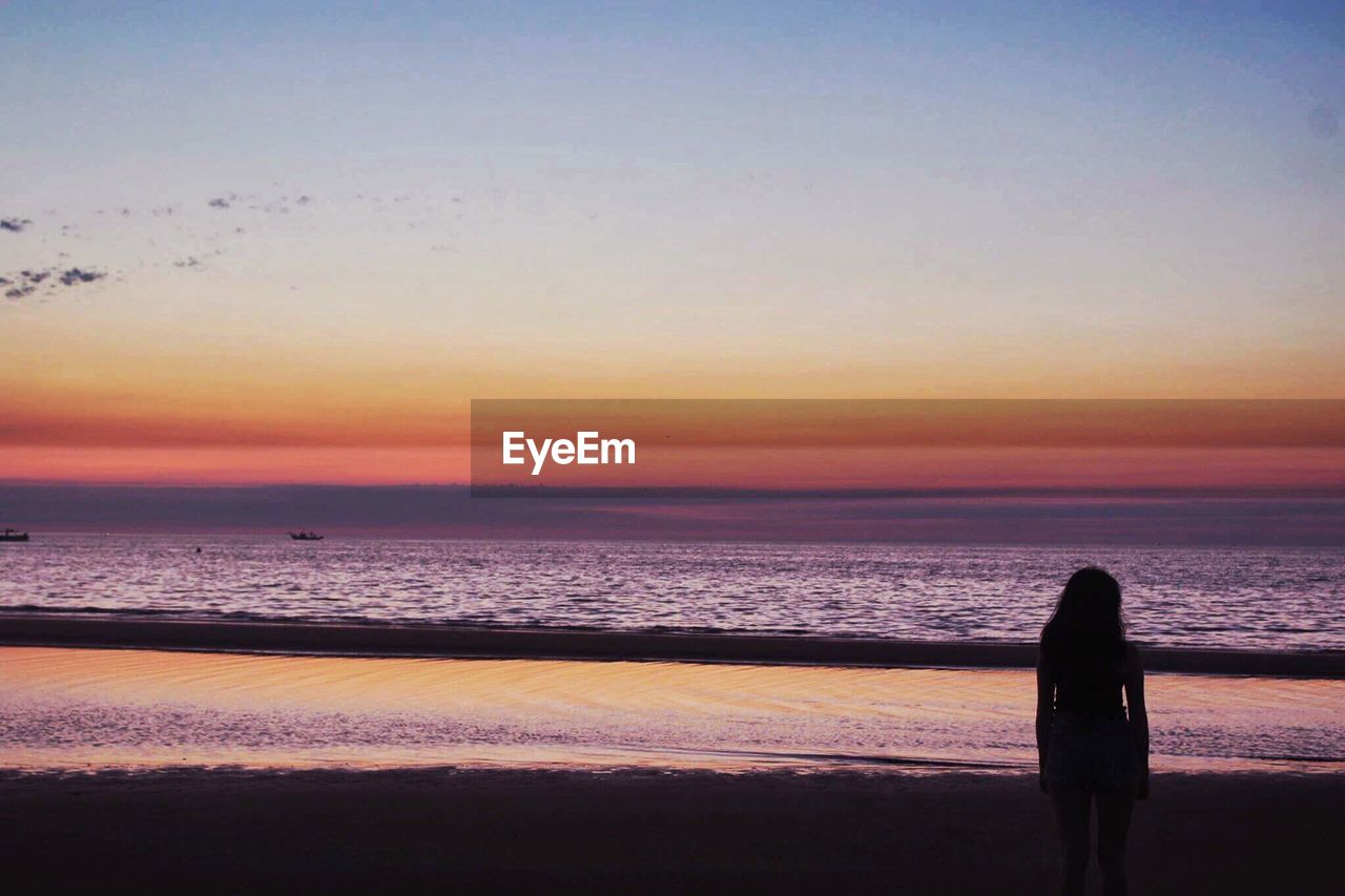 Woman Standing At Sea Shore Against Clear Sky During Sunset