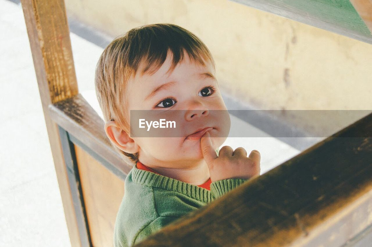 High angle view of boy looking up while thinking at home