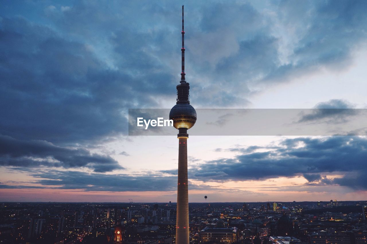 Fernsehturm Against Cloudy Sky During Sunset In City