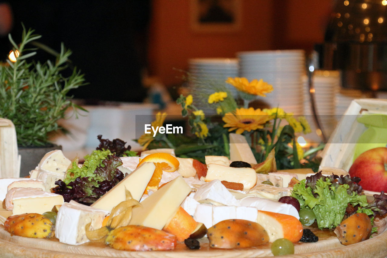 Close-up of fruit salad with cheese in plate at buffet