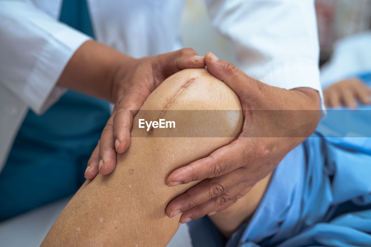 Midsection of doctor holding patients knee