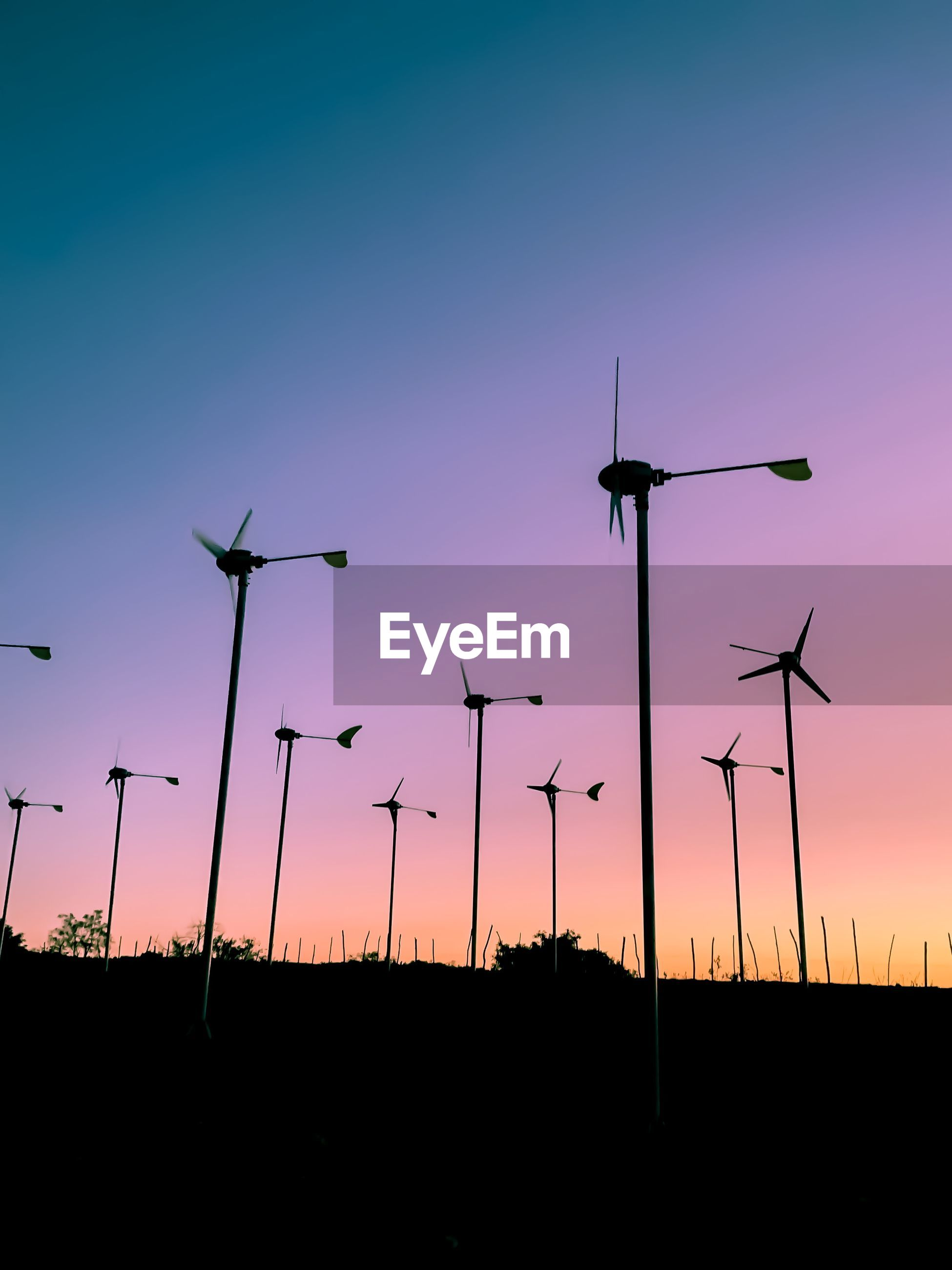 SILHOUETTE WINDMILLS ON FIELD AGAINST SKY DURING SUNSET