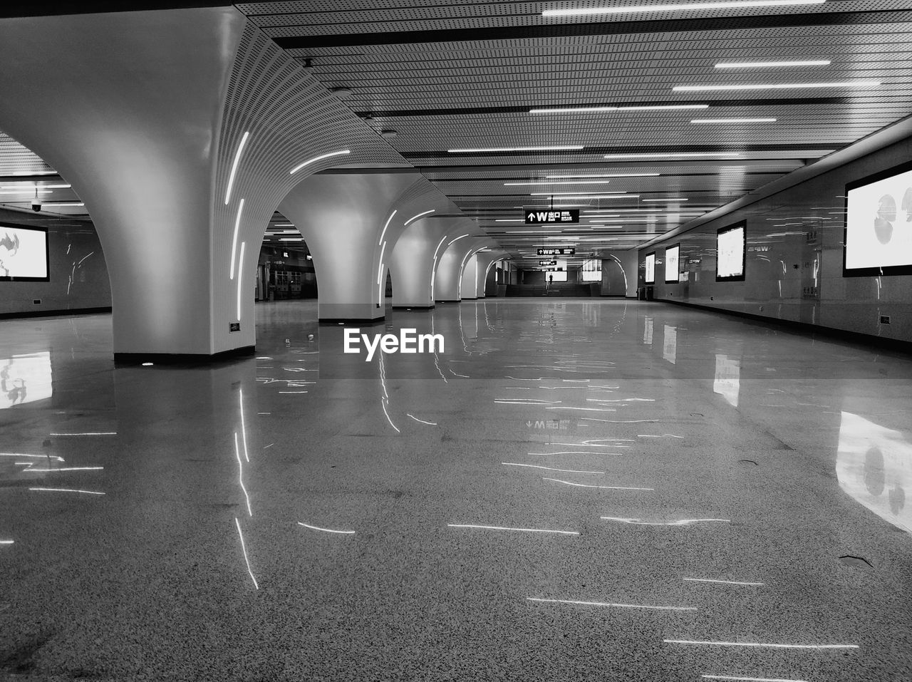illuminated, architecture, indoors, transportation, built structure, empty, ceiling, flooring, direction, the way forward, architectural column, sign, no people, public transportation, reflection, lighting equipment, building, subway, symbol, absence, diminishing perspective, modern, parking garage, surface level, tiled floor, long