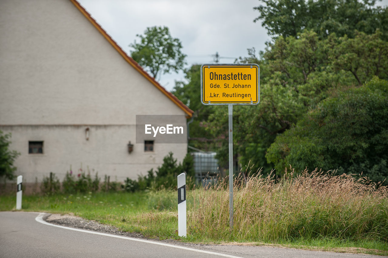 sign, communication, plant, road, no people, tree, architecture, built structure, building exterior, transportation, day, text, focus on foreground, warning sign, information, nature, building, house, direction, guidance, outdoors