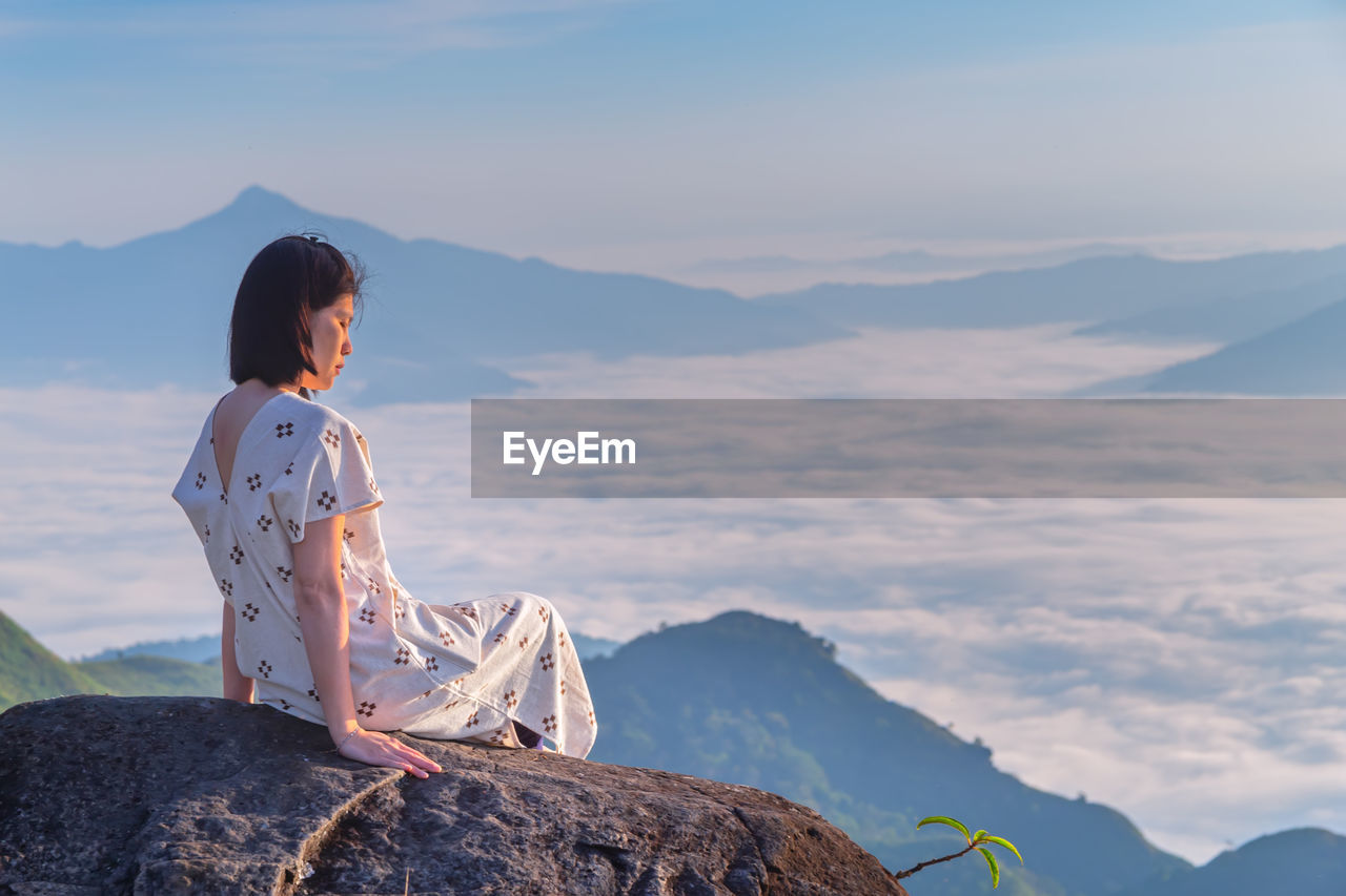 Woman looking at cloudscape during sunset