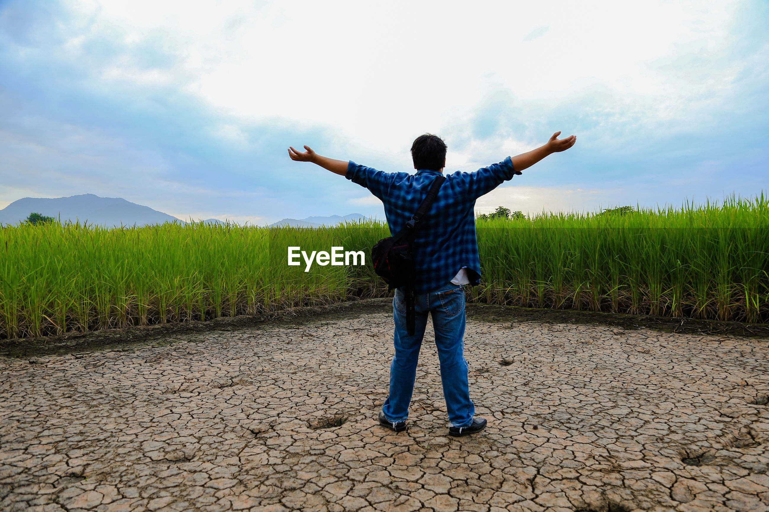 Rear view of man with arms outstretched standing on dry field against sky