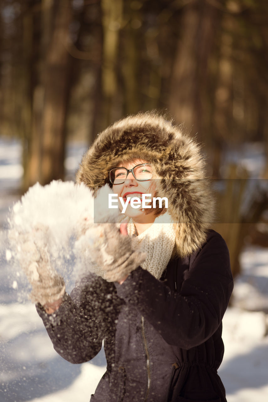 Young Woman Throwing Snow On Field