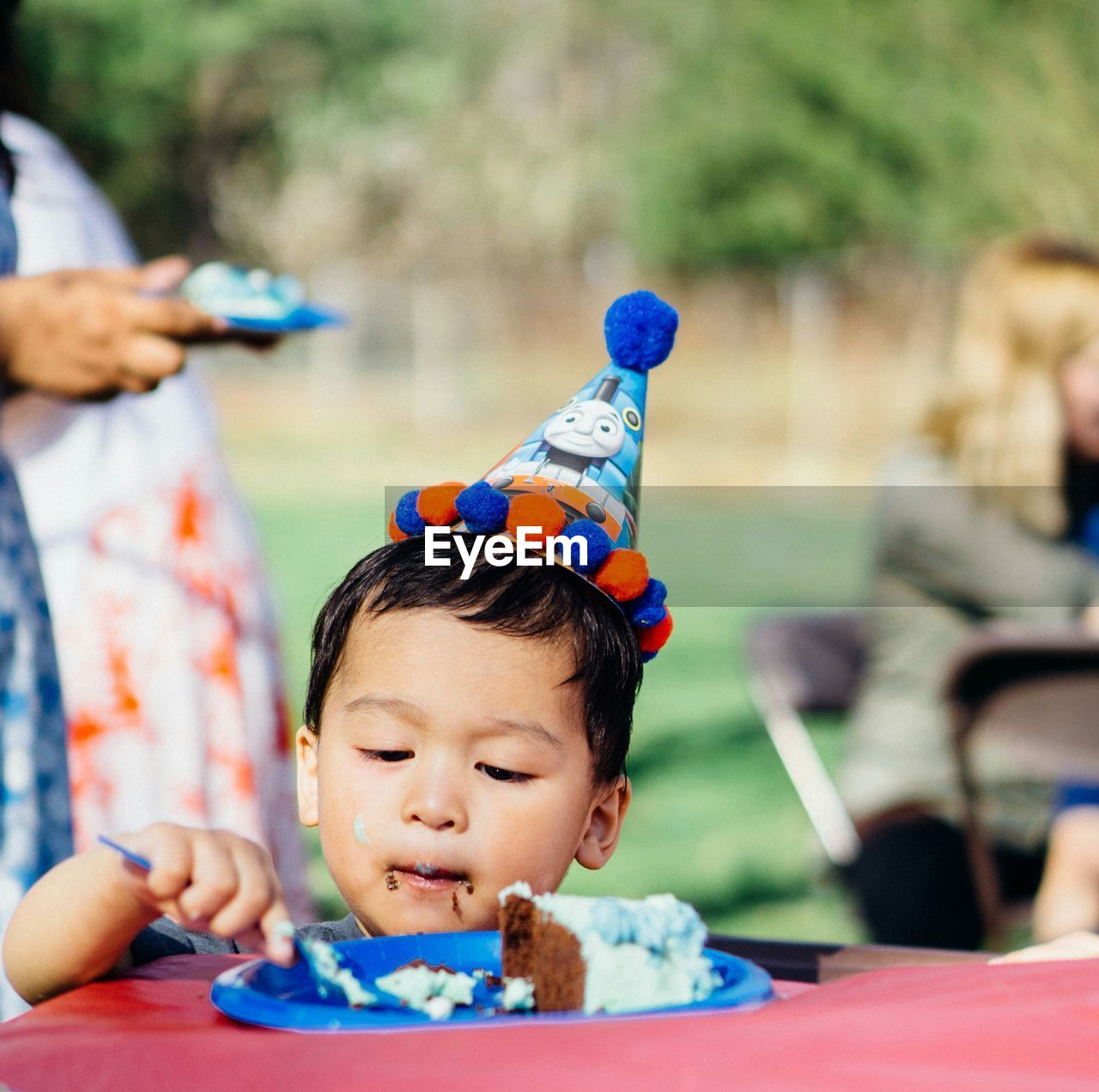 Boy In Party Hat Eating Cake