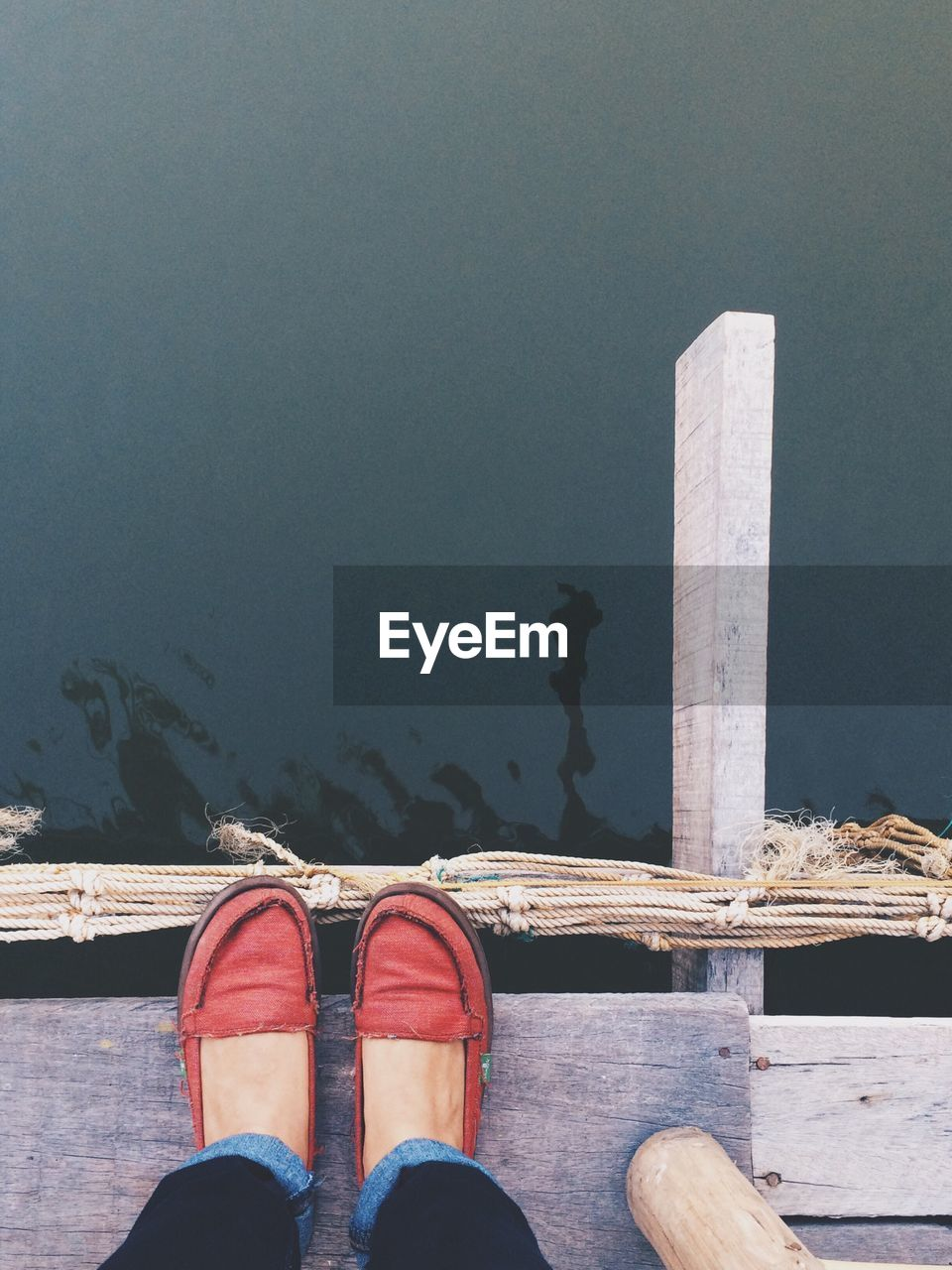 Low Section Of Woman Wearing Shoes Standing On Pier