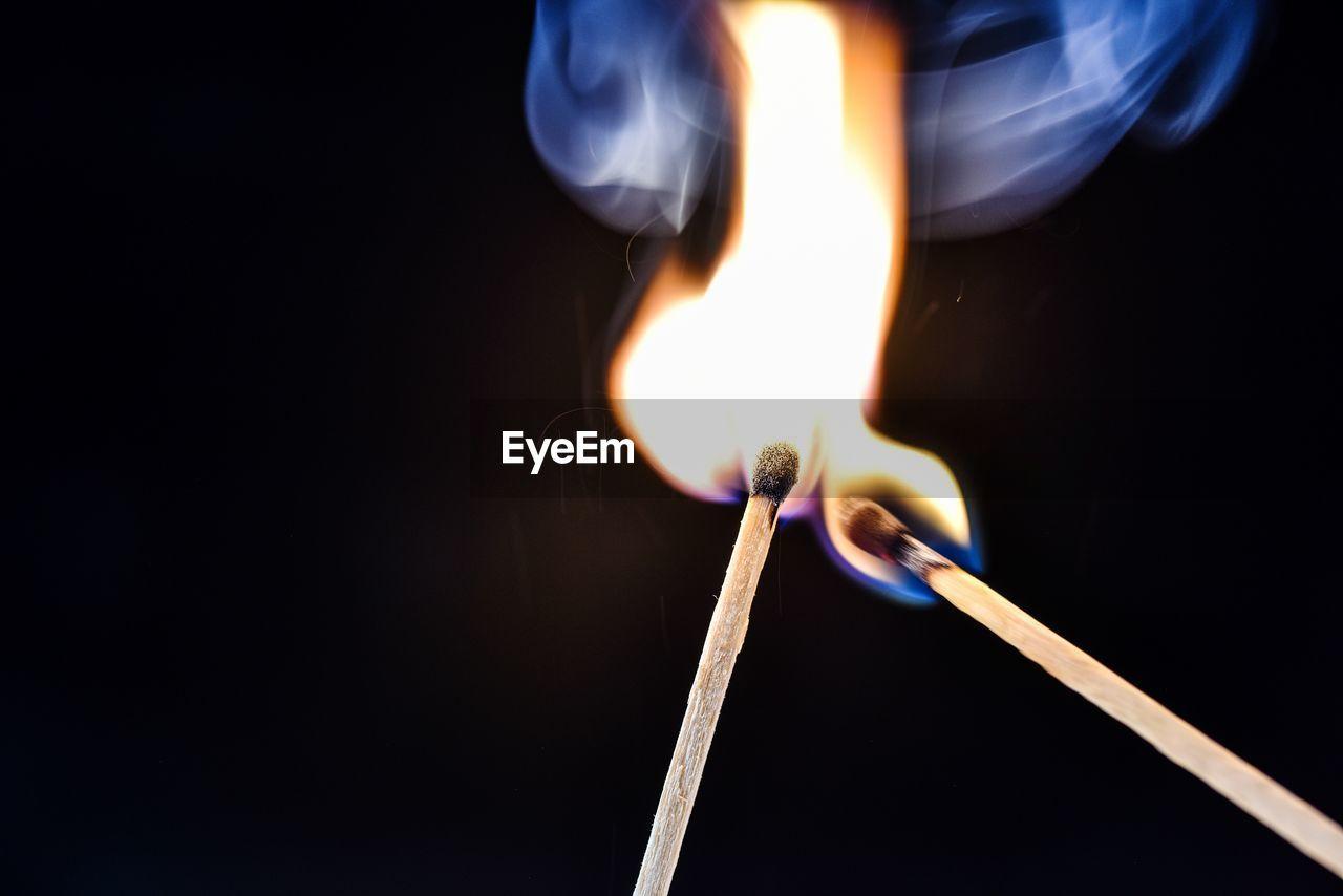 Close-up of burning matchsticks against black background
