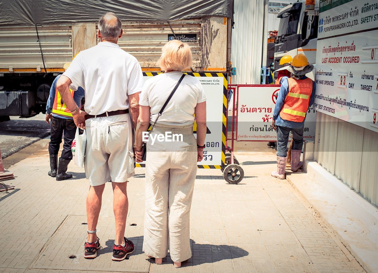 occupation, men, full length, group of people, adult, real people, senior adult, standing, transportation, people, rear view, safety, clothing, working, protection, reflective clothing, cooperation, architecture, teamwork, mature men, uniform, responsibility
