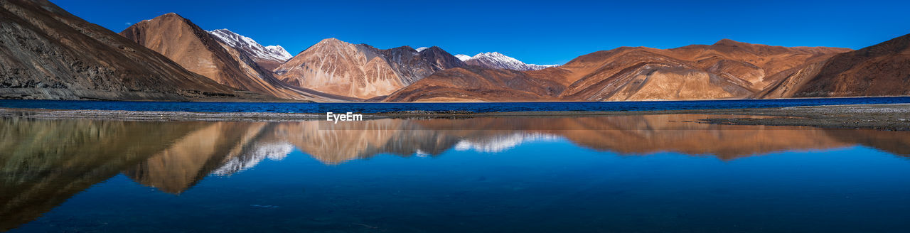 REFLECTION OF MOUNTAINS ON LAKE AGAINST BLUE SKY