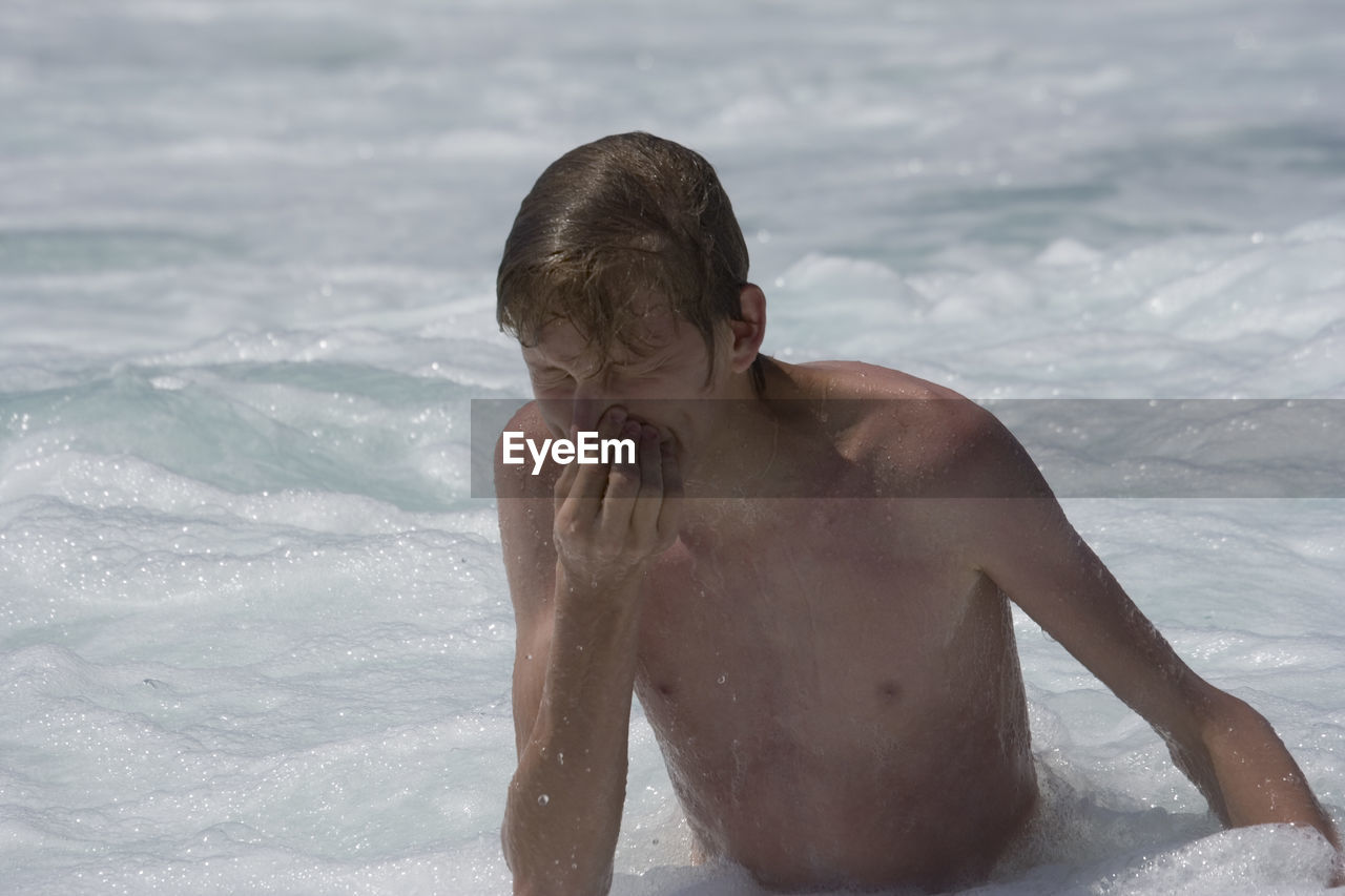 High angle view of shirtless man holding his nose with eyes closed in sea at beach