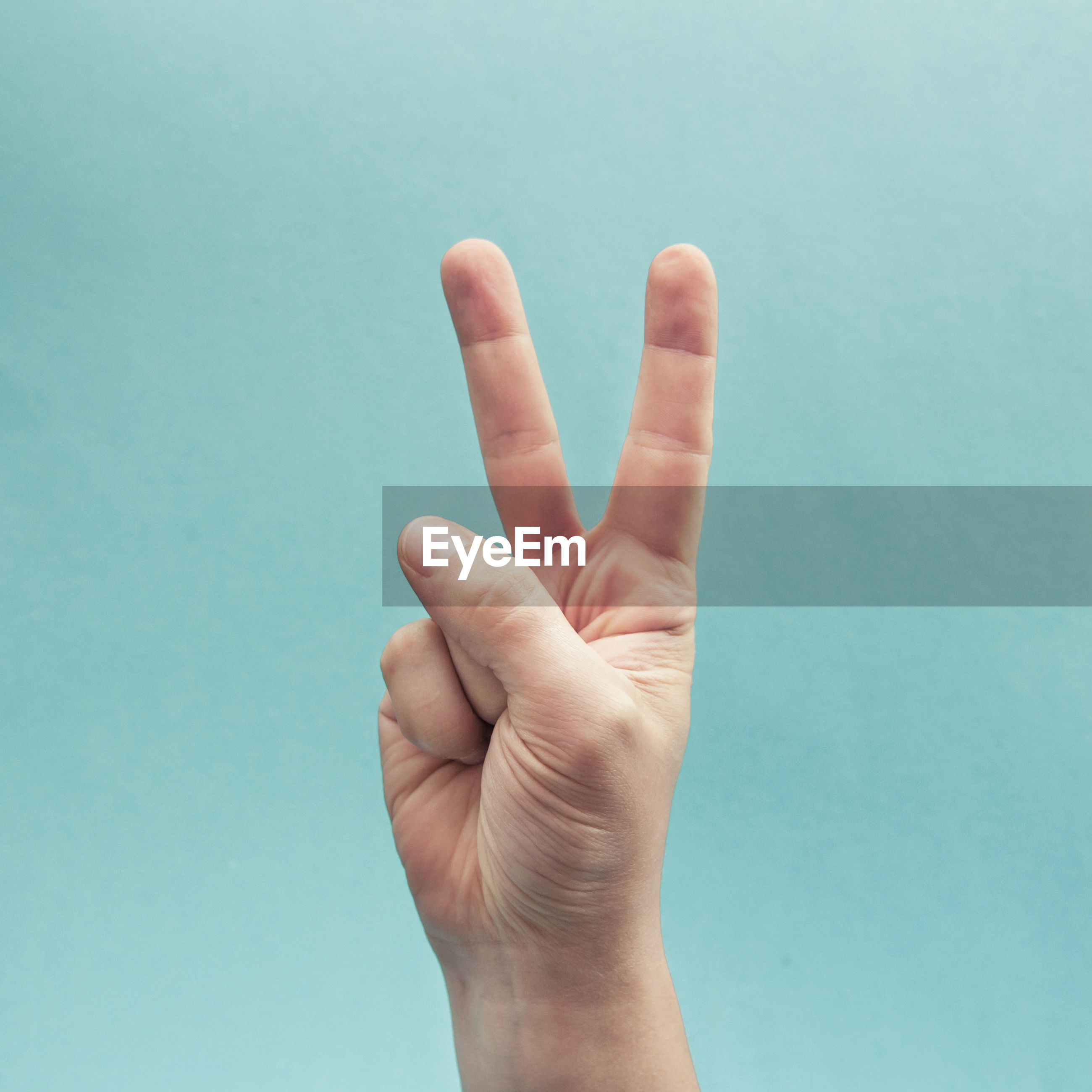 Cropped hand gesturing against turquoise background
