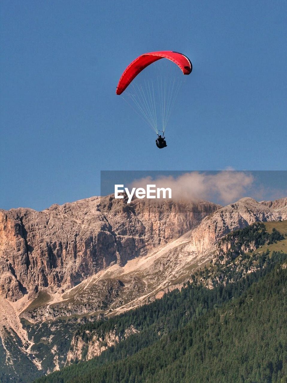 Person Paragliding Above Forest Trees And Mountains Against Sky