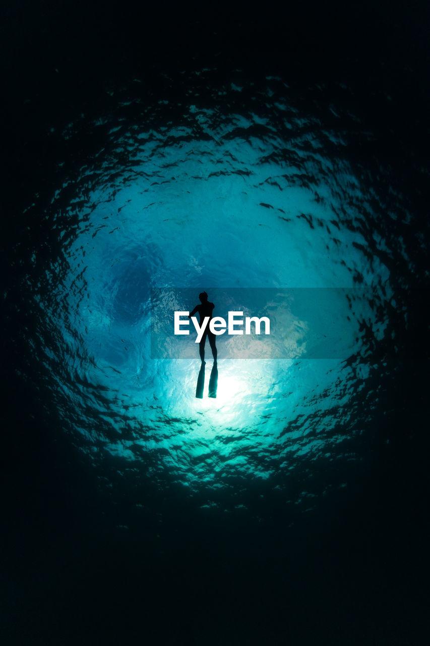 Silhouette person swimming undersea