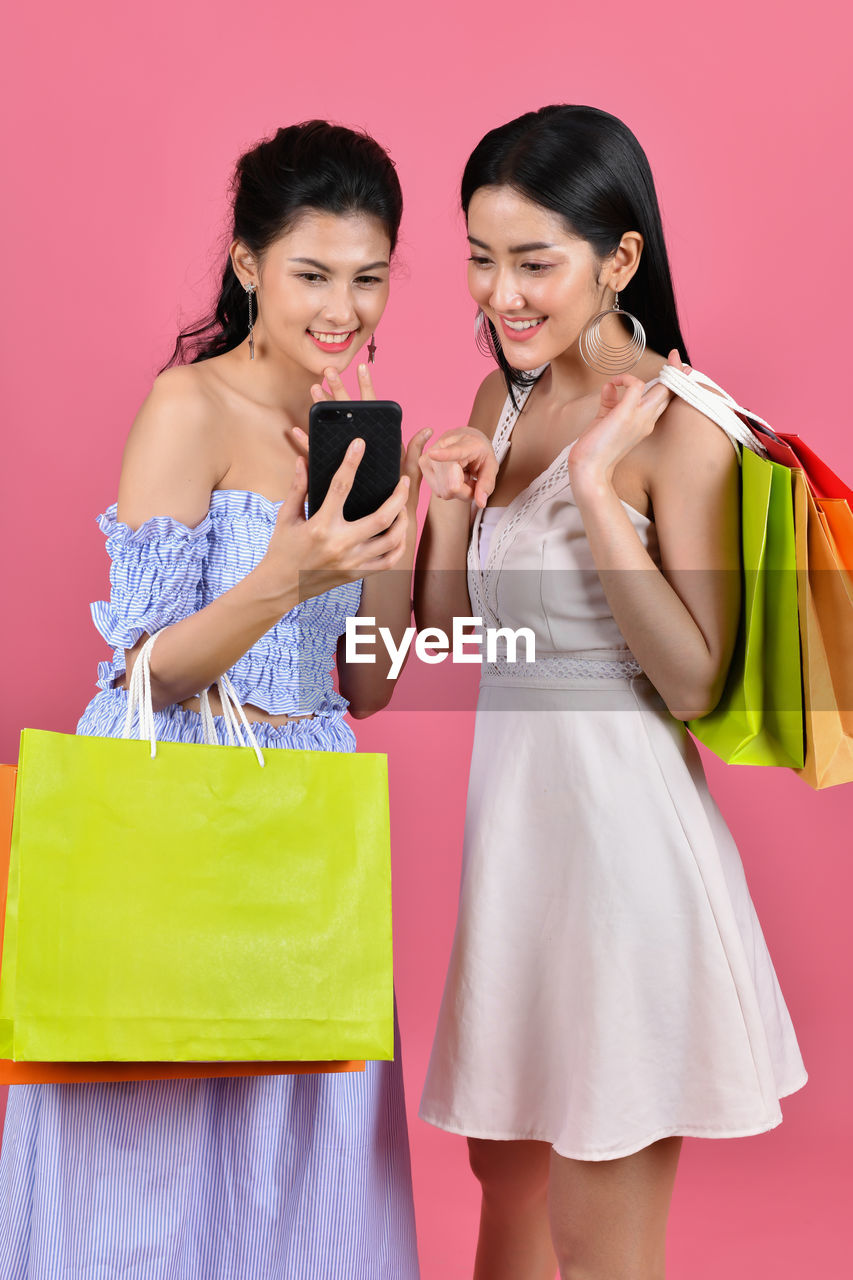 Smiling Female Friends Using Mobile Phone While Holding Shopping Bags Against Coral Background