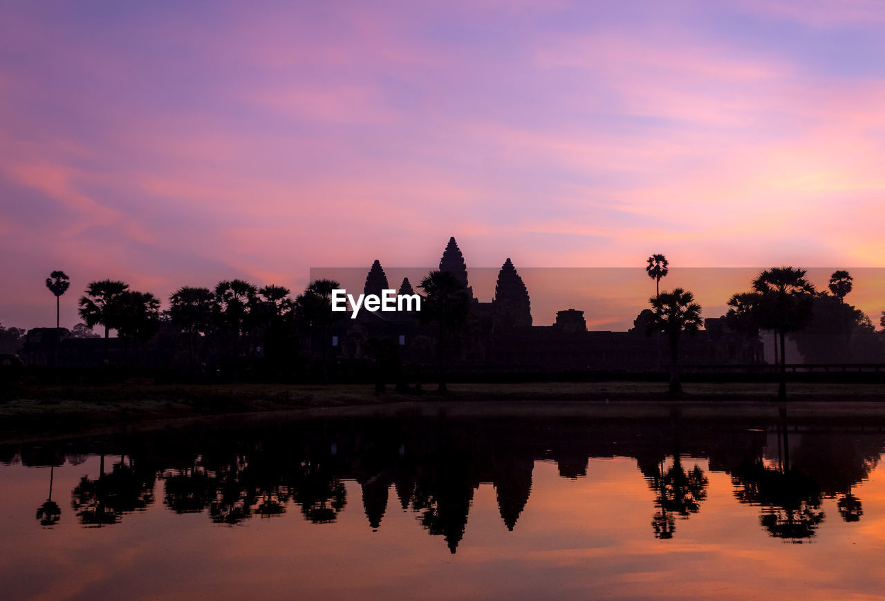 Silhouette trees by angkor wat against cloudy sky during sunset