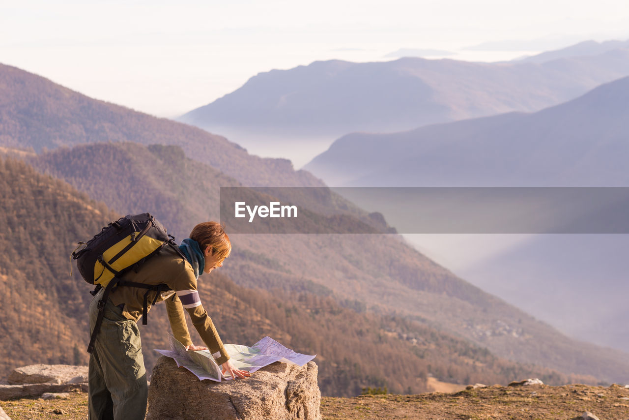 Woman Looking At Map On Landscape
