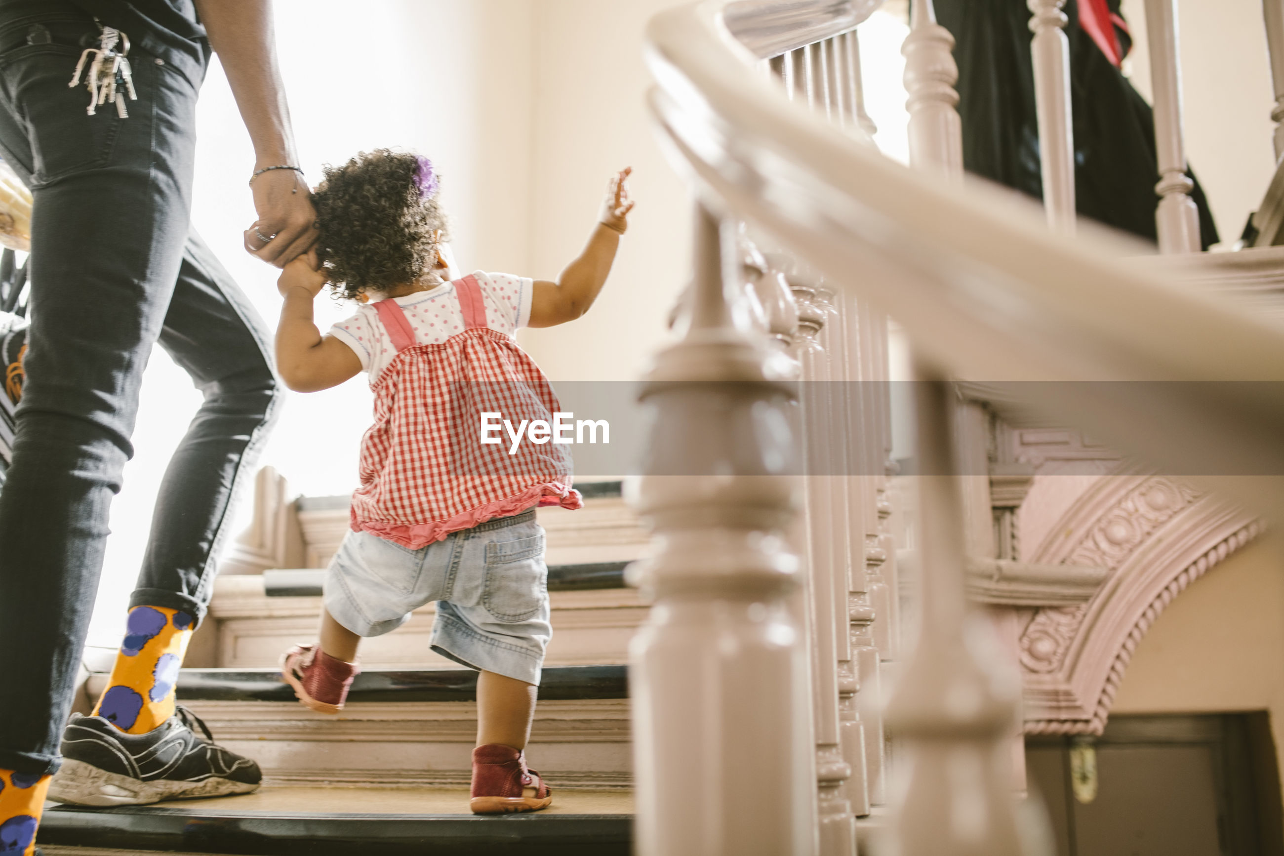 Baby girl holding hand of father while climbing steps in apartment