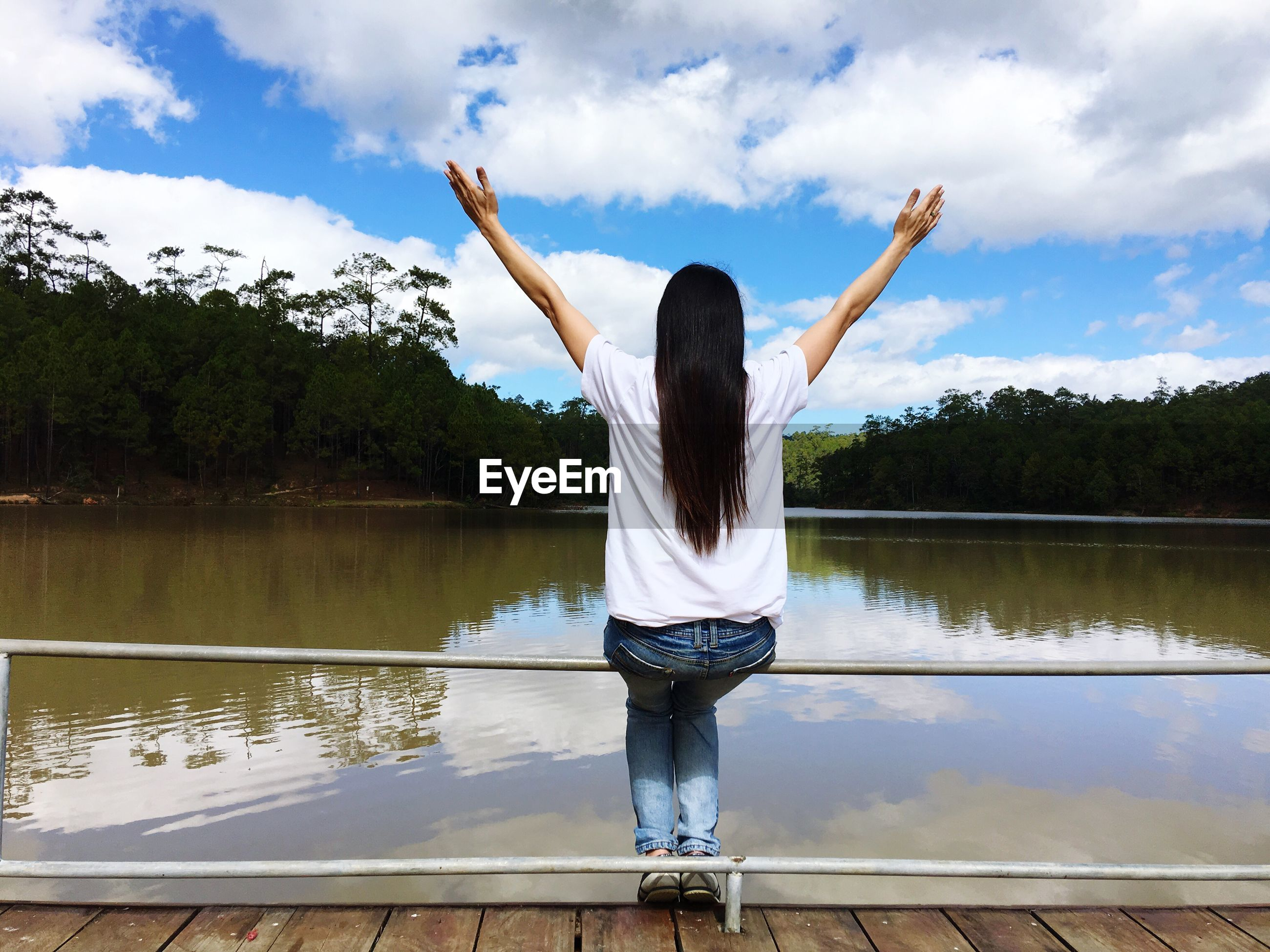 Rear view of woman with arms raised sitting by lake against sky
