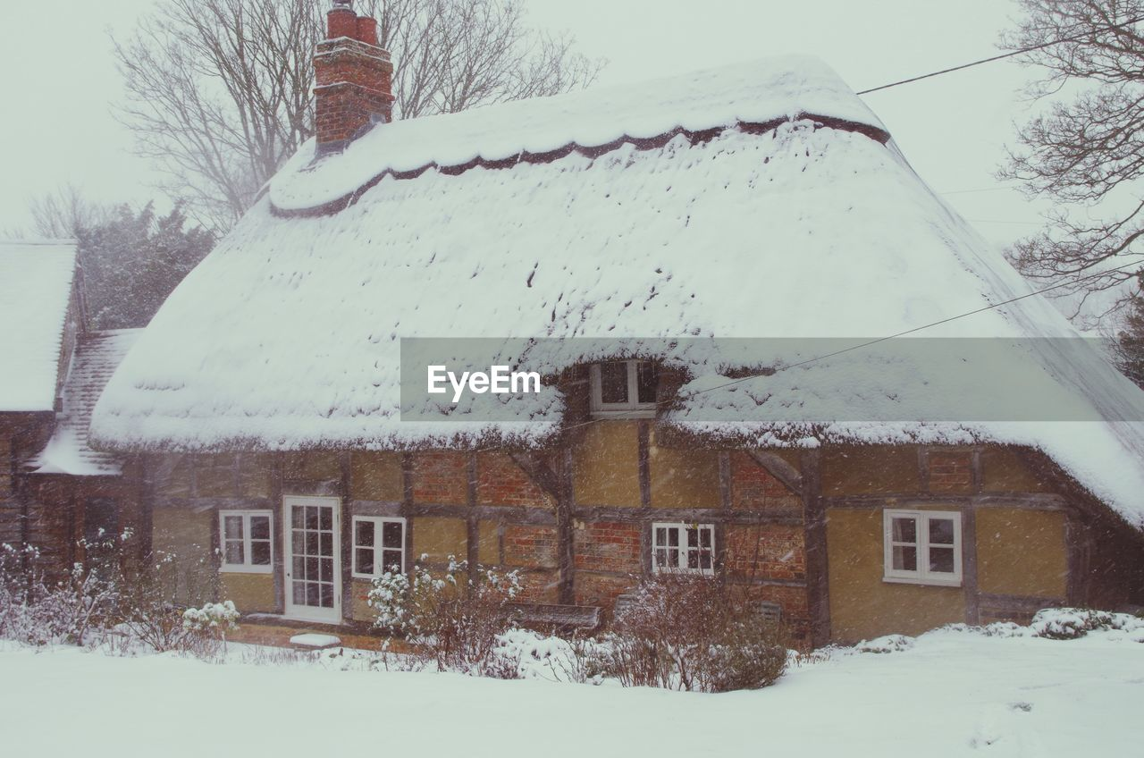 winter, snow, cold temperature, weather, building exterior, house, built structure, architecture, snowing, frozen, nature, residential building, outdoors, snowfall, tree, bare tree, no people, day, roof, snowdrift, beauty in nature, sky, tiled roof