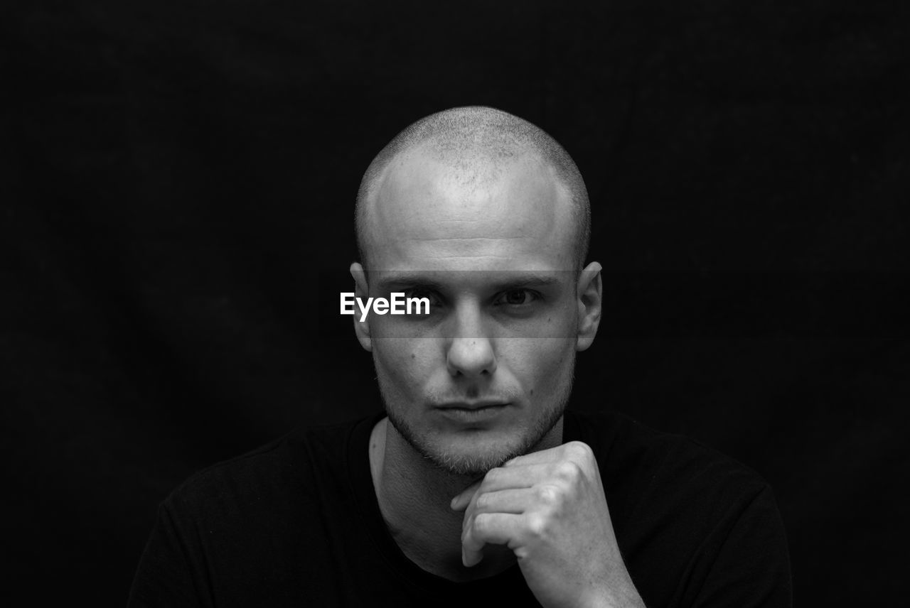 Portrait Of Man With Shaved Head Against Black Background