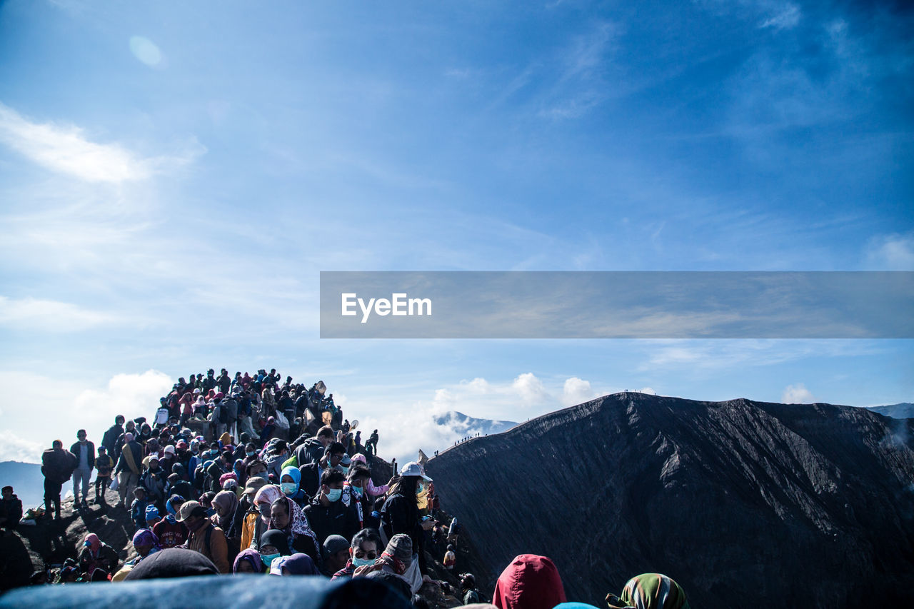 People On Mountain Against Blue Sky During Sunny Day