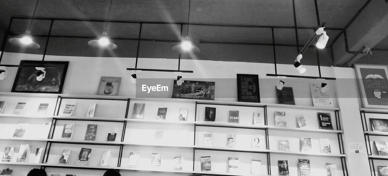 indoors, lighting equipment, illuminated, no people, hanging, shelf, architecture, low angle view, bookshelf, day