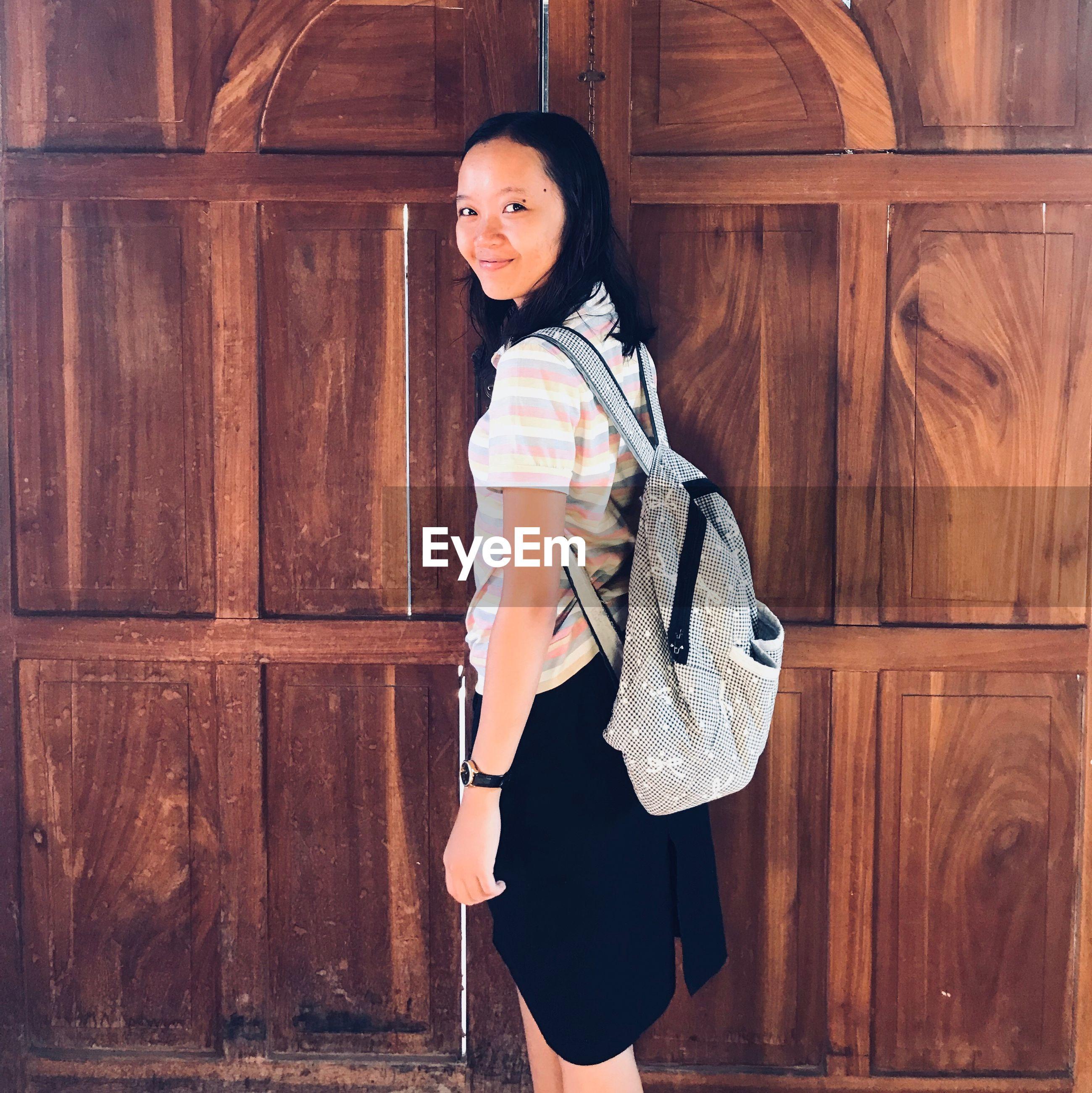 Portrait of woman standing by closed wooden door
