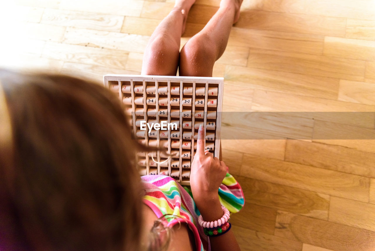 indoors, leisure activity, women, flooring, human body part, child, holding, hardwood floor, wood, lifestyles, real people, people, human hand, two people, girls, childhood, hand, high angle view, playing