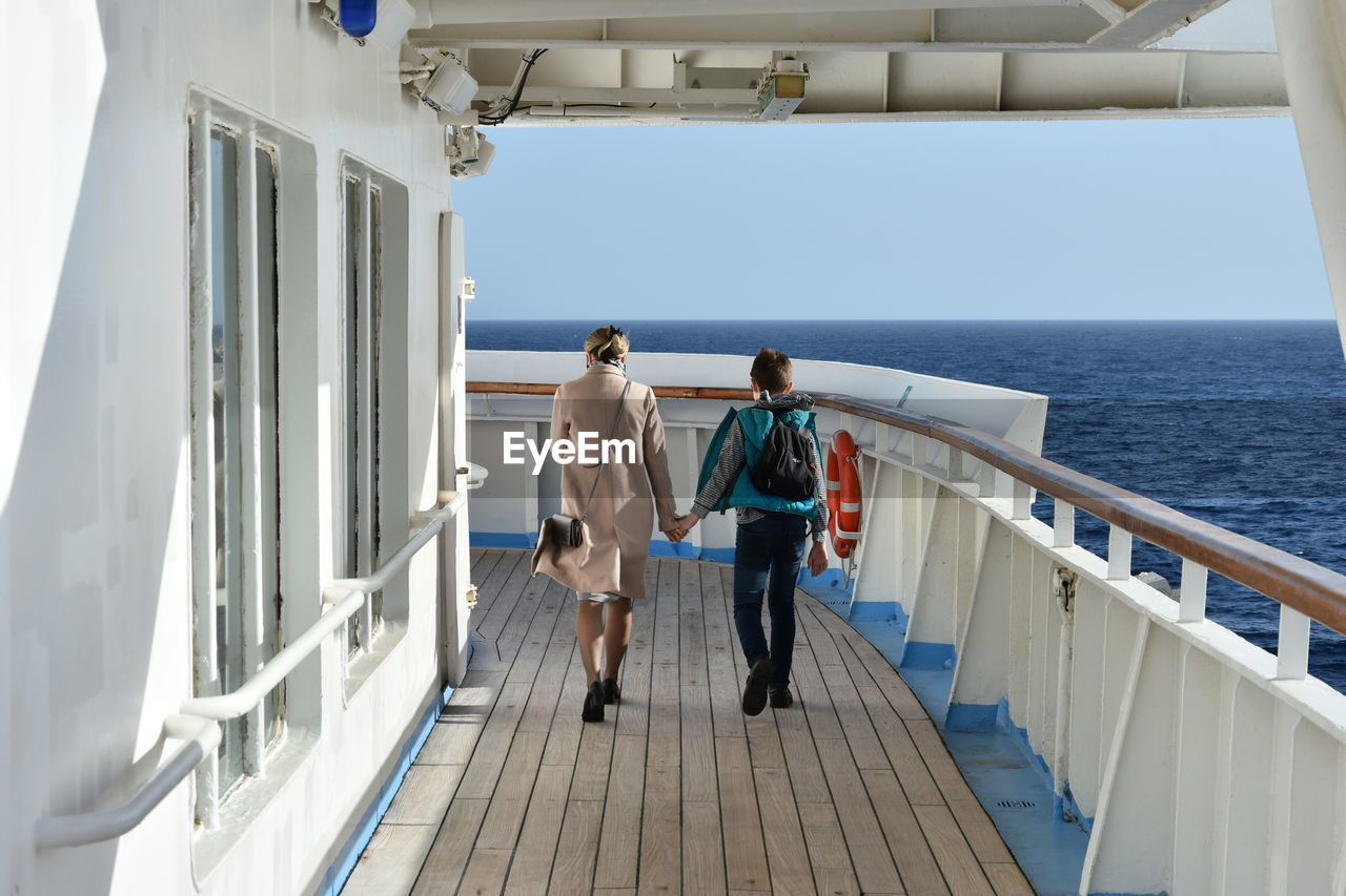 Rear view of mother and son walking on boat deck