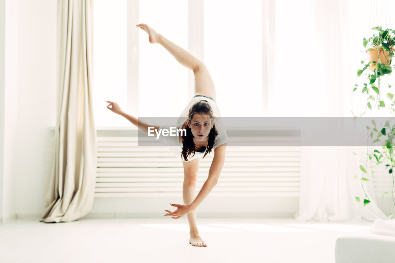 Full Length Portrait Of Young Woman Practicing Yoga In Warrior Position At Home